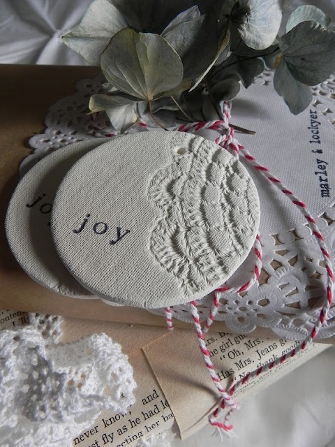 Use air-dry clay, rolled out (3-5mm thick). Press linen or cotton for texture.  Press doily for imprint. Cut out the shape. Use a nail for hole. Use rubber stamp letters (joy, love, peace, noel etc.) Let the ornament dry completely.  Paint the ornament with white acrylic paint or leave it natural. Fill in the imprint of the word with a darker shade of paint.