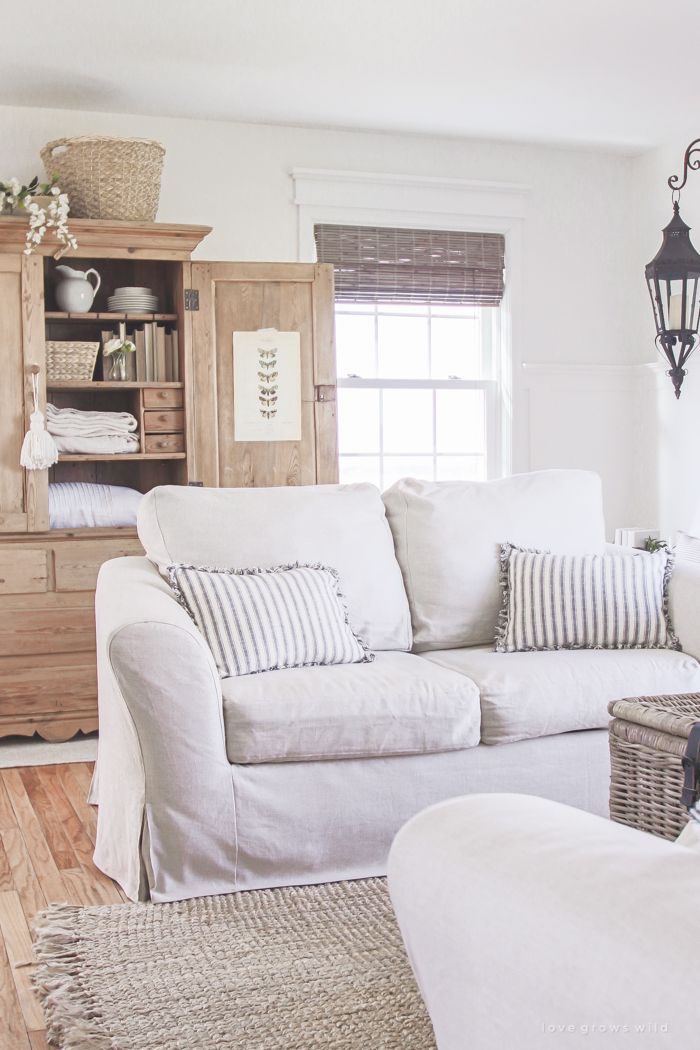 A cozy farmhouse living room with beautiful linen slipcovered sofas. See how to get this custom slipcovered look at LoveGrowsWild.com!