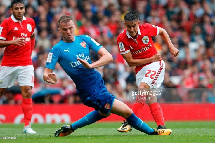 Benfica's Argentinian striker Franco Cervi (R) shoots past Arsenal's English defender Rob Holding to score the opening goal of the pre-season friendly football match between Arsenal and Benfica at The Emirates Stadium in north London on July 29, 2017, the game is one of four matches played over two days for the Emirates Cup. / AFP PHOTO / Ian KINGTON / RESTRICTED TO EDITORIAL USE. No use with unauthorized audio, video, data, fixture lists, club/league logos or 'live' services. Online…