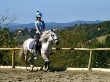 A young rider enjoying a riding lesson with an amazing view of the tuscan hills at Il Paretaio a classical riding center near Florence, what fun!