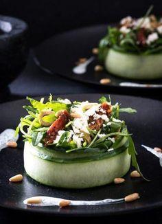 Heerlijke salade met feta en zongedroogde tomaten: Mooi voorgerecht dat makkelijk te maken is van komkommer, rucola, olijven en zongedroogde tomaatjes. Ingrediënten: Komkommer - 1 Rucola - 50 gram Groene olijven