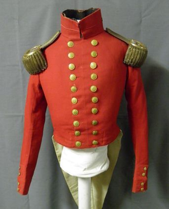 Red woollen tailored double breasted Royal Army Medical Corps officer's jacket with stand up collar, waist length at front and split tails at back, with long sleeves slightly gathered at shoulders. The collar has decorative cord detail and buttons.