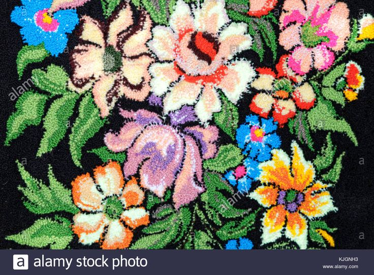 Download this stock image: Crafts: beautiful red, blue and yellow flower embroidered on a black background. - KJGNH3 from Alamy's library of millions of high resolution stock photos, illustrations and vectors.