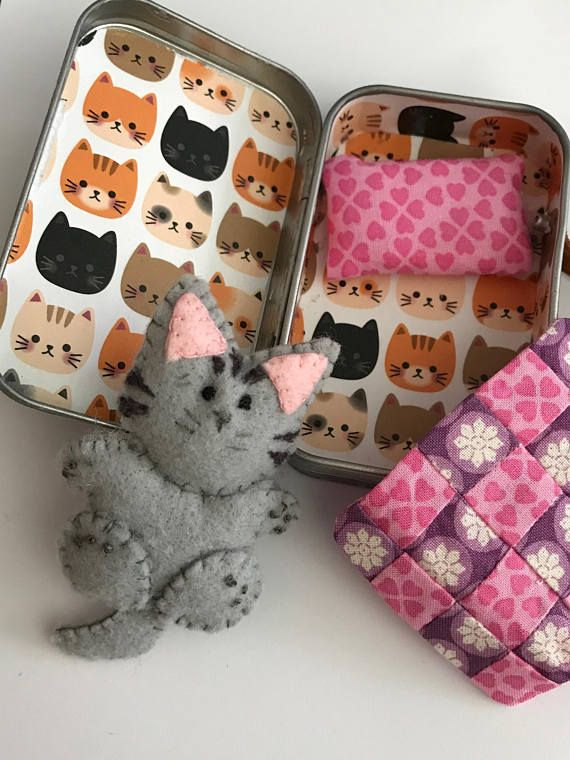 3 Felt Kitten, Sits inside an altoid Tin. Outside tin is covered in black with gold dots, inside is white with kitten faces. Handmade pink and purple quilt (2 1/2 x 2 1/4) along with a pink pillow Handle is made of leather and permanently attached.