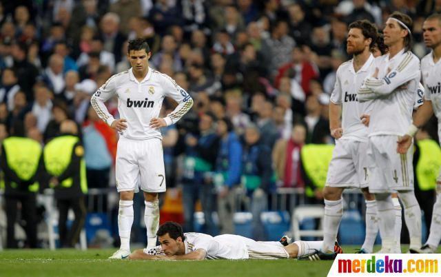 Cristiano Ronaldo bersedih, sementara rekan-rekannya tercenung.