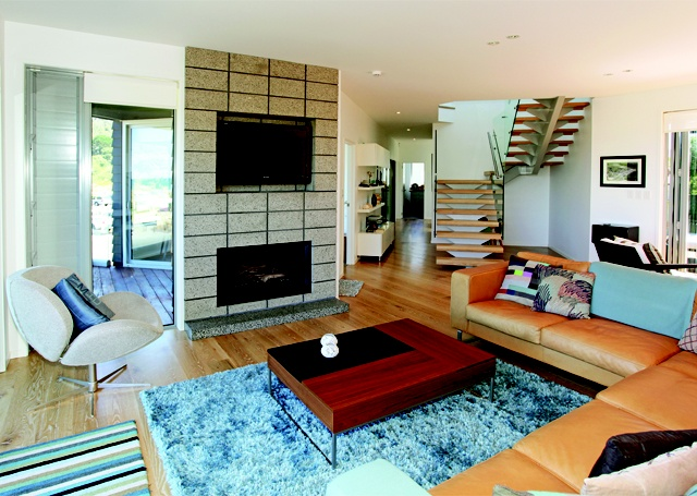 The home's colour palette and furnishings echo its coastal surrounds. The floating staircase is the feature of the living area.