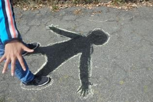 Have one kid pose in the sun while another kid colors in the shadow with chalk