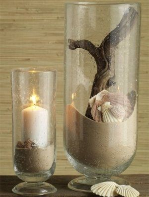 Beautiful beach memories display. Sand, a candle, seashells, and a piece of driftwood in vases. Nice!