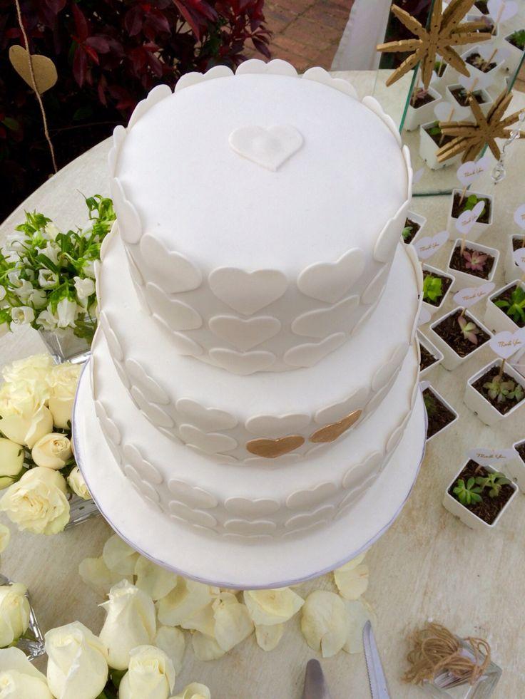 White theme outdoor garden wedding. Cake table with white wedding cake with hearts.