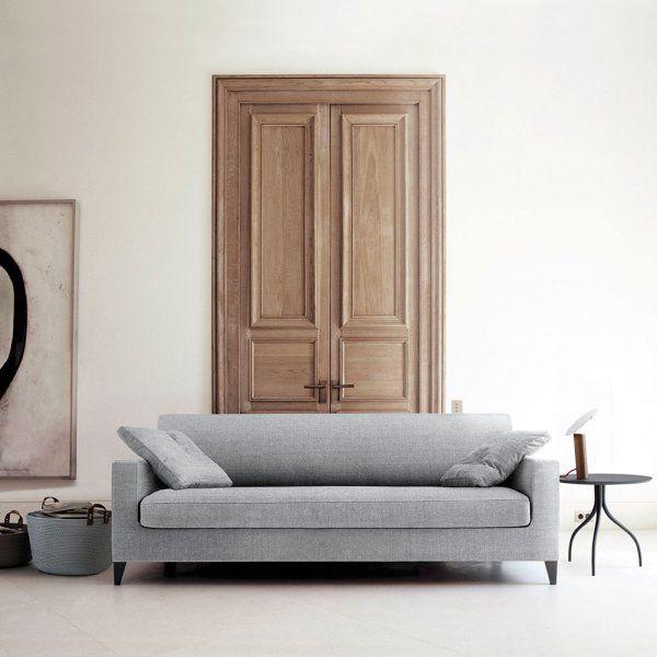 Pour adopter un style minimaliste dans votre intérieur, optez pour du mobilier aux lignes épurées comme ce canapé et cette table d'appoint aux lignes courbes.