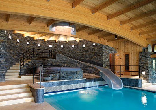 tastefully done indoor pool with water slide and hot tub
