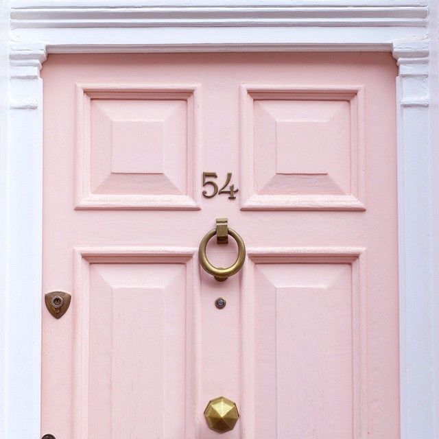 Love the soft pink door and brass hardware with the white surround.