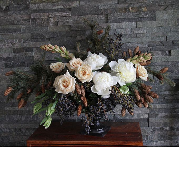 Brides.com: Winter Wedding Flowers. Wedding centerpiece of privet berries, pine boughs, pinecones, roses, peonies, tuberoses, and parrot tulips by Honey of a Thousand Flowers Browse more rustic wedding centerpieces.