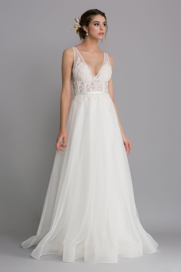 A sheer v-neckline on a soft tulle bodice, this dress is a structured style with a sheer bodice, and is finished with appliqued beaded lace detailing.  The full skirt flares and folds in a soft silhouette.  A ribbon sash is tied at the back of the gown to finish the waist perfectly.  Colours available - Cream (only)