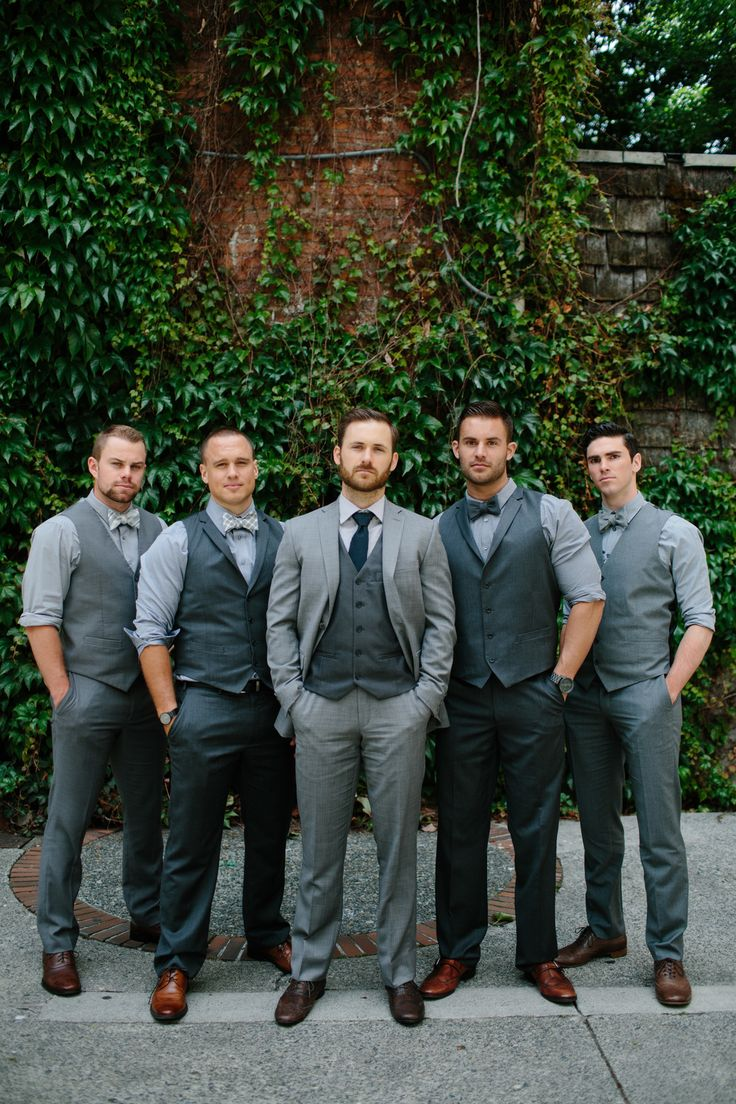 The groom looks distinct from his groomsmen. Here, the groom wears a suit jacket and traditional tie, while the guys don vests and bowties.