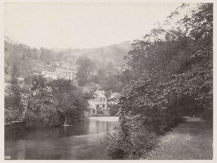 Anonymous   Panoramisch uitzicht op huizen tegen een heuvelrug aan een water in Matlock, op de voorgrond een overgroeid pad, Anonymous, 1878 - 1890   Onderdeel van Reisalbum Europese steden, vermoedelijk Zweeds.