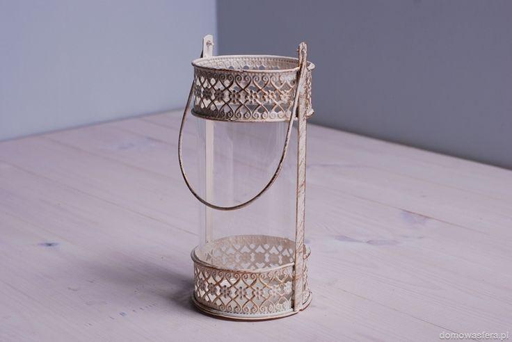 Piękny lampion wykonany z cienkiego metalu z wybitym kwiatowym ażurem (przez co rzuca niezwykłe cienie). Lampion posiada metalowy uchwyt, dzięki temu możemy powiesić go na ogrodzie lub tarasie.  Wewnątrz znajduje się szklana tuba, która chroni płonień świecy.