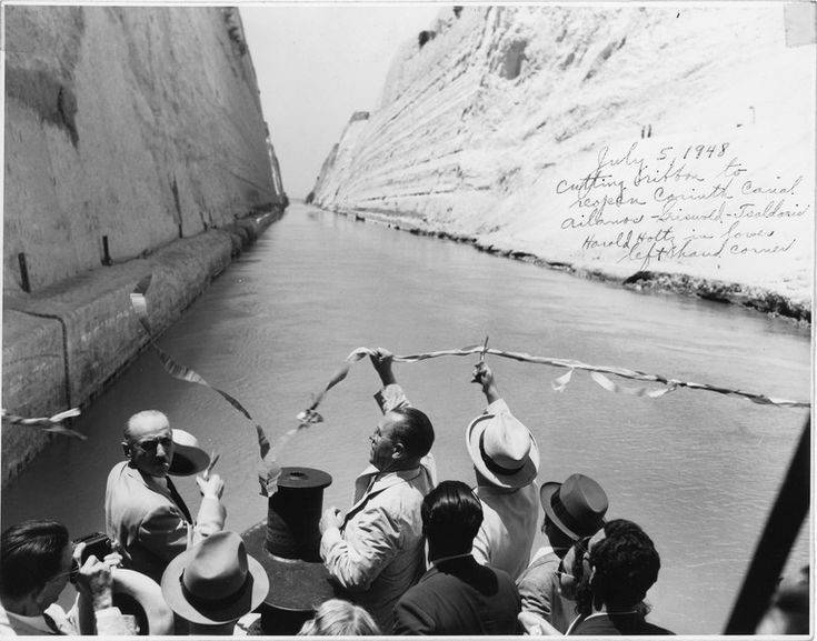 Ailanos (left, holding hat) and Constantine Tsaldaris (right, in white hat, facing away from camera) cut the ribbon held by Dwight Griswold (center), Chief of the American Mission for Aid to Greece, to reopen the Corinth Canal in Greece connecting the Gulf of Corinth with the Saronic Gulf in the Aegean Sea. Harold Holtz, a member of Griswold's staff, stands in the lower left hand corner of the photograph with other unidentified men. Date: July 5, 1948