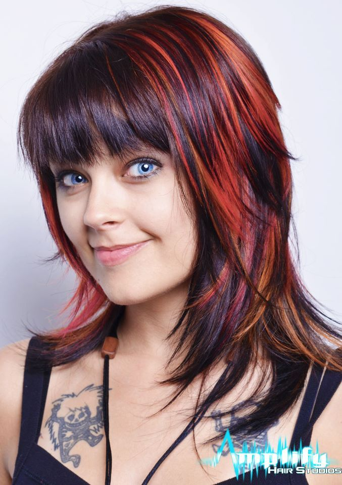 A medium to long hairstyle with a soft bang, lots of layering and texture. This haircut is complimented with funky watermelon and yellow highlights.