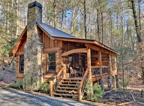 Northern Georgia's Blue Ridge Mountains play host to a cozy cabin in the woods. A large stone chimney anchors one end of the gable design, which also includes an extended porch roof across the front. Resting on stone piers, the raised porch features balustrades with decorative twig work.
