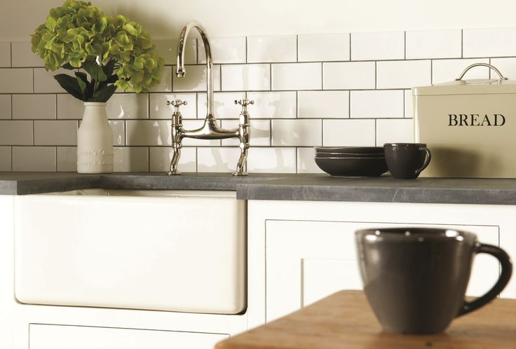 Helmingham glossy white brick tiles coupled with dark grout is a timeless look as a kitchen splashback, but would also work in bathrooms. Handmade ceramic tiles, made in the UK. winchestertiles.com
