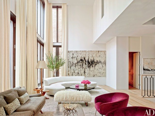 In the double-height living room of decorator Laura Santos's Manhattan townhouse, a curvaceous Vladimir Kagan sofa is arranged with a vintage cocktail table from Galerie Van den Akker, a 1940s French floor lamp, and a Dune bench upholstered in Mongolian lamb; the diptych is by Mark Francis.