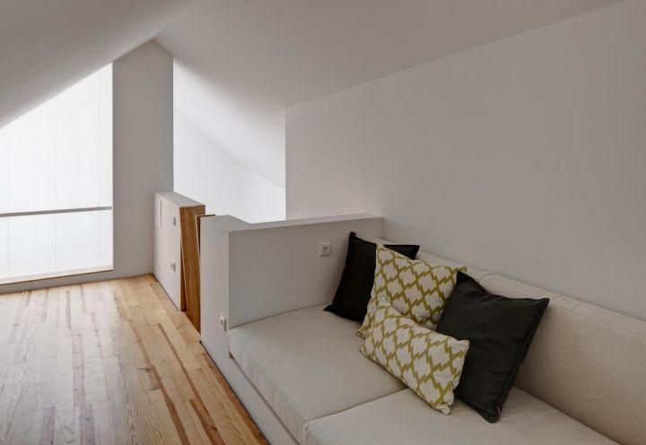 Un soppalco sottotetto ha permesso di creare un ulteriore spazio vivibile, adibito a sala relax e studio. Divano total white su disegno degli architetti dello studio Ezzo