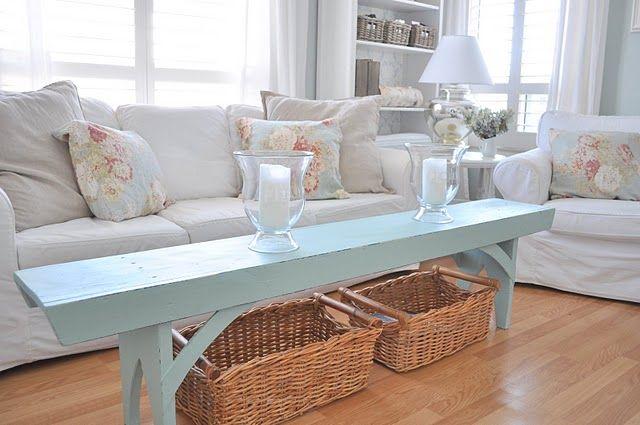 Outra mesa de centro improvisada: um banco simples pintado e cestos para revistas e almofadas