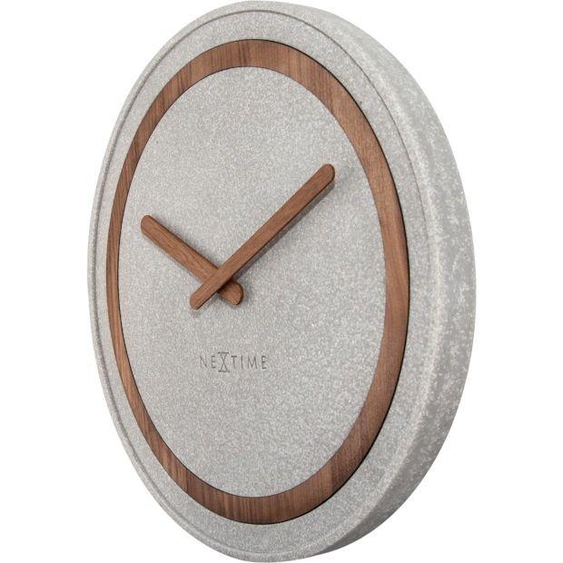 Met deze Concreto wandklok van NeXtime geef je je interieur in een mum van tijd een stoere impuls. De klok is gemaakt van polyresin met een grijze kleur. Door de lichte kleurverschillen in de grijze behuizing lijkt de klok net van robuust beton. De wijzerplaat is afgewerkt met een houten cirkel en houten wijzers, waardoor de klok een stoere en natuurlijke uitstraling heeft. Hang de klok in je woonkamer en geniet van het prachtige design. De klok meet Ø39,5 cm en heeft een stil uurwerk.