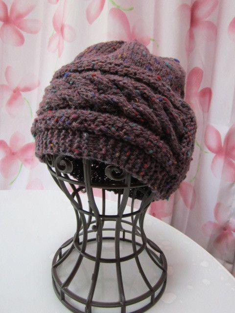 縄編み2本のベルトのようなデザインが特徴の手編み帽子です。木ボタンがついたフラップがアクセントです。こちらの毛糸は、紫地に、オレンジ・グリーンなどのゴマが入っ... ハンドメイド、手作り、手仕事品の通販・販売・購入ならCreema。