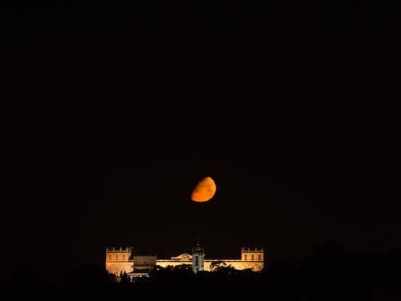 orange moon over the palace in a summer