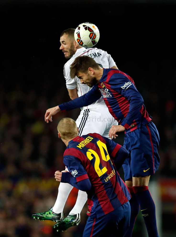Karim Benzema of Real Madrid CF competes for the ball against Gerard Piqué of FC Barcelona during the La Liga match between FC Barcelona and Real Madrid CF at Camp Nou on March 22, 2015 in Barcelona, Spain.