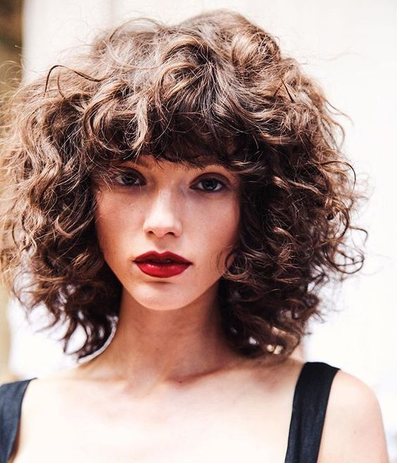 Although my hair is not this thick, it could be grown out to this medium, curly, layered hair cut with heavy bangs.