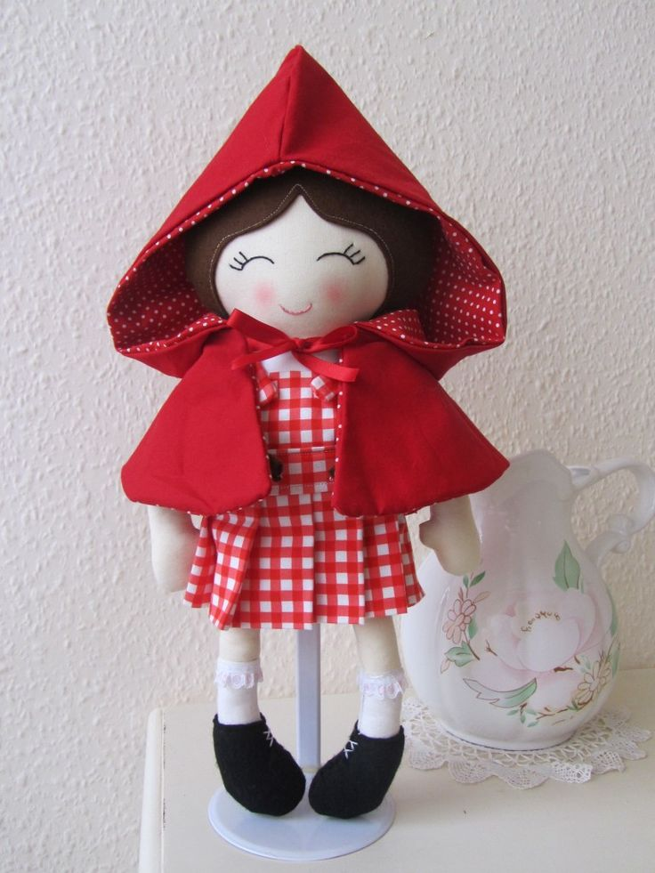 Handmade fabric doll made suing designer cottons and 100% wool felt. Little Red has sewn on sleeves, a red gingham removable pinafore dress, sewn on black boots and brown pigtails. Her red hooded cape is reversible and removable. She is just over 40cm tall and her face has been hand embroidered. She is CE marked and suitable from birth.