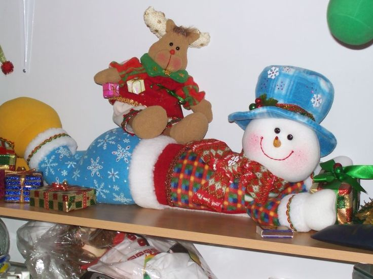 Muñeco de nieve aperezado y reno sentado sobre él.