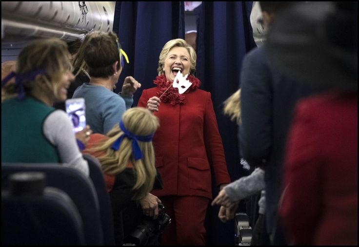 Holding a halloween mask, @Hillary Clinton jokes with her staff who were wearing halloween costumes on board her last flight of the day.