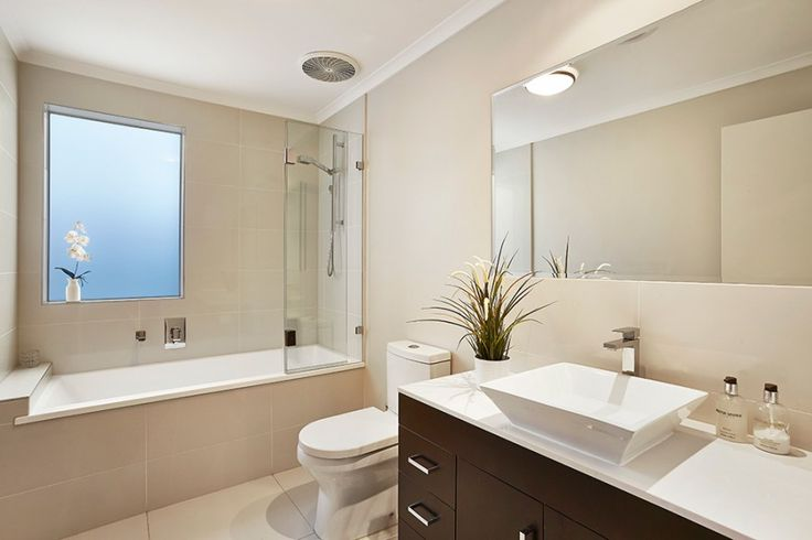 Lovely neutral colours timeless bathroom, brown cabinetry and indoor plants.