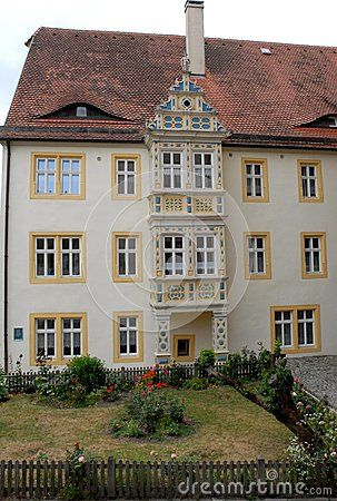 Photo made at a delicate white gate and porch like milk in the city of Augsburg in Bavaria (Germany). In the picture you see the open gate in wrought iron, with a coat of arms in the top, allowing you to enter the long portico from the white walls of the garden.