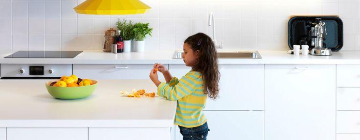 Dívka loupající pomeranč v bílé kuchyni IKEA
