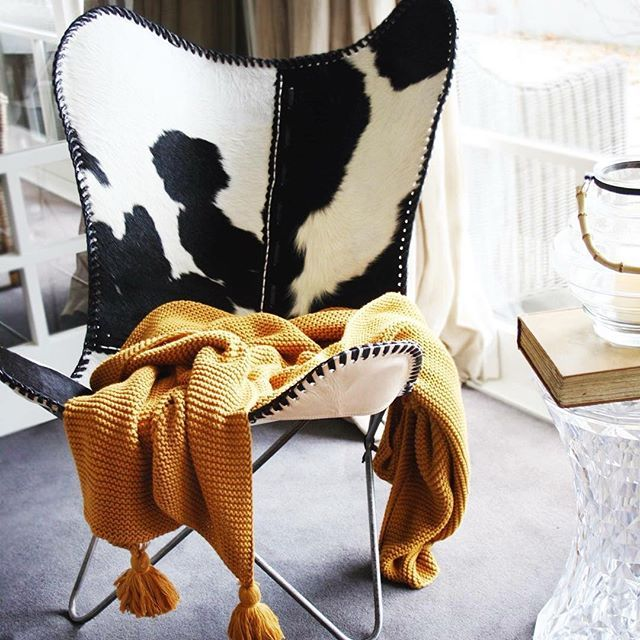 Our Redcurrent Cowhide Butterfly Chair is the perfect occasional chair for any room in the home priced at $595.00. Redcurrent Mustard Tassel Throw $145.00.