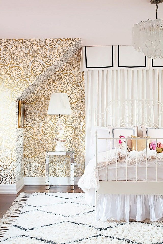 Children's bedroom with gold and white wallpaper, and a white metal bed frame