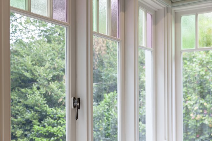 Traditional casement windows with colonial bars and coloured glass and teardrop casement openers