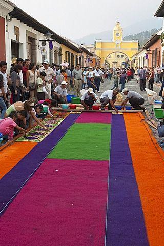 Las personas que trabajan en una alfombra hecha de arena y serrín a lo largo del recorrido procesional el Viernes Santo.  Fabricación de alfombras es considerado como un acto de sacrificio, como el detalle elaborado y hora en que entra en la fabricación de alfombras es una manera para que la gente dé algo de themselv