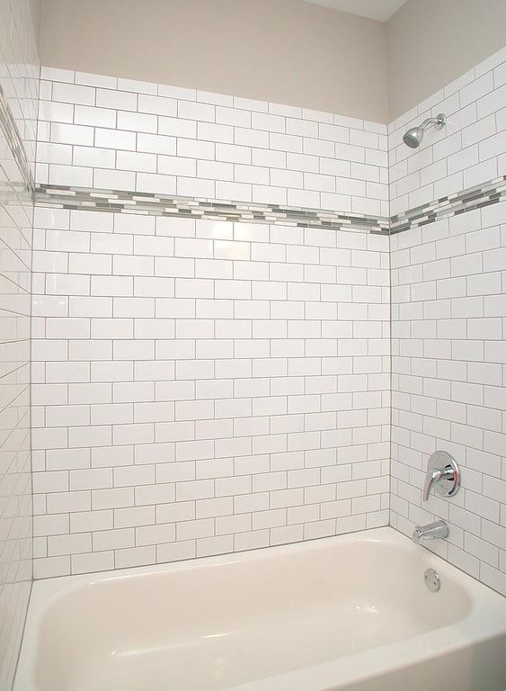 """Contemporary Full Bathroom - Found on Zillow Digs. This tile surround features 3x6 White Ice Brick Laid Subway tile with Deloreon Gray grout. The 3"""" glass accent tile is Zumpano Iceland Bliss. Designed and Built by Epic Development; Photo by OBEO"""