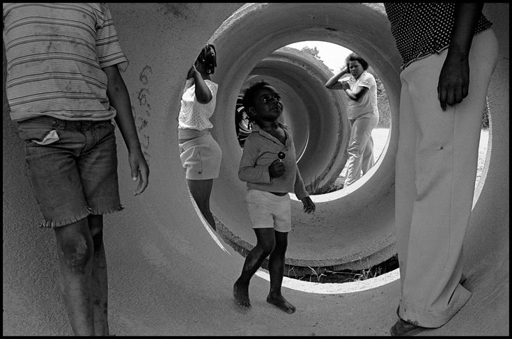 Alex Webb USA. Mississippi. Mound Bayou. 1976. Playing in an unused sewer pipe.