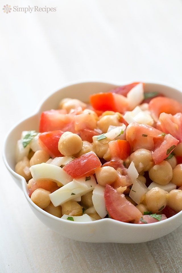 Chickpea tomato salad with fresh summer tomatoes, garbanzo beans, hard boiled eggs, onions, and parsley, and tossed with a light vinaigrette. So EASY! Quick summer salad. On SimplyRecipes.com
