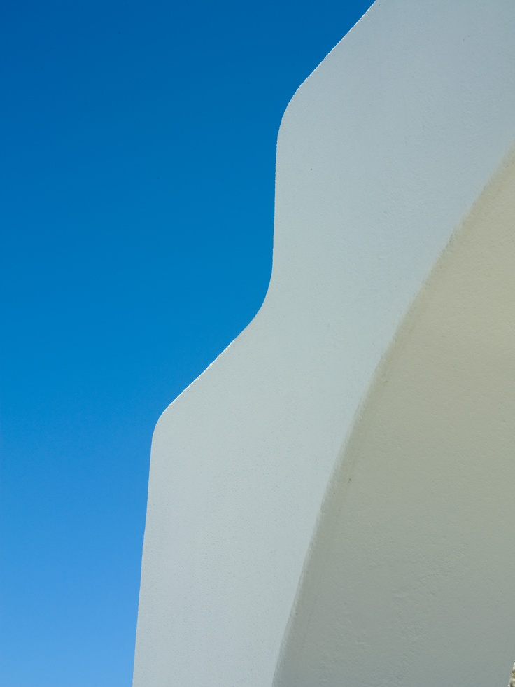 The bold blue of sky against the smoothing white edge of a chimney at Mykonos Grand Luxury Hotel