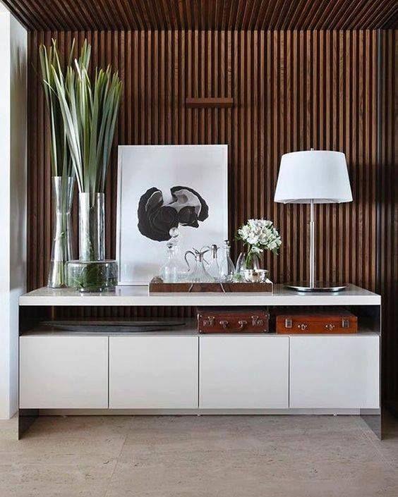 Aparador laqueado em frente ao painel ripado, clean, moderno e lindo para receber o uso como bar também! Autor Desconhecido