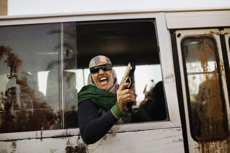 An armed female supporter of Colonel Qaddafi chants pro-regime slogans during a demonstration in favor of the Libyan leader in Tripoli's Green Square, Libya, 2011.