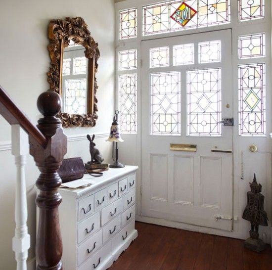 Maintaining an original hallway feature, such as these beautiful stained glass panels, is well worth it; as light filters through, it bathes the hall in soft pink tones and highlights the intricate detailing on the ornate mirror.